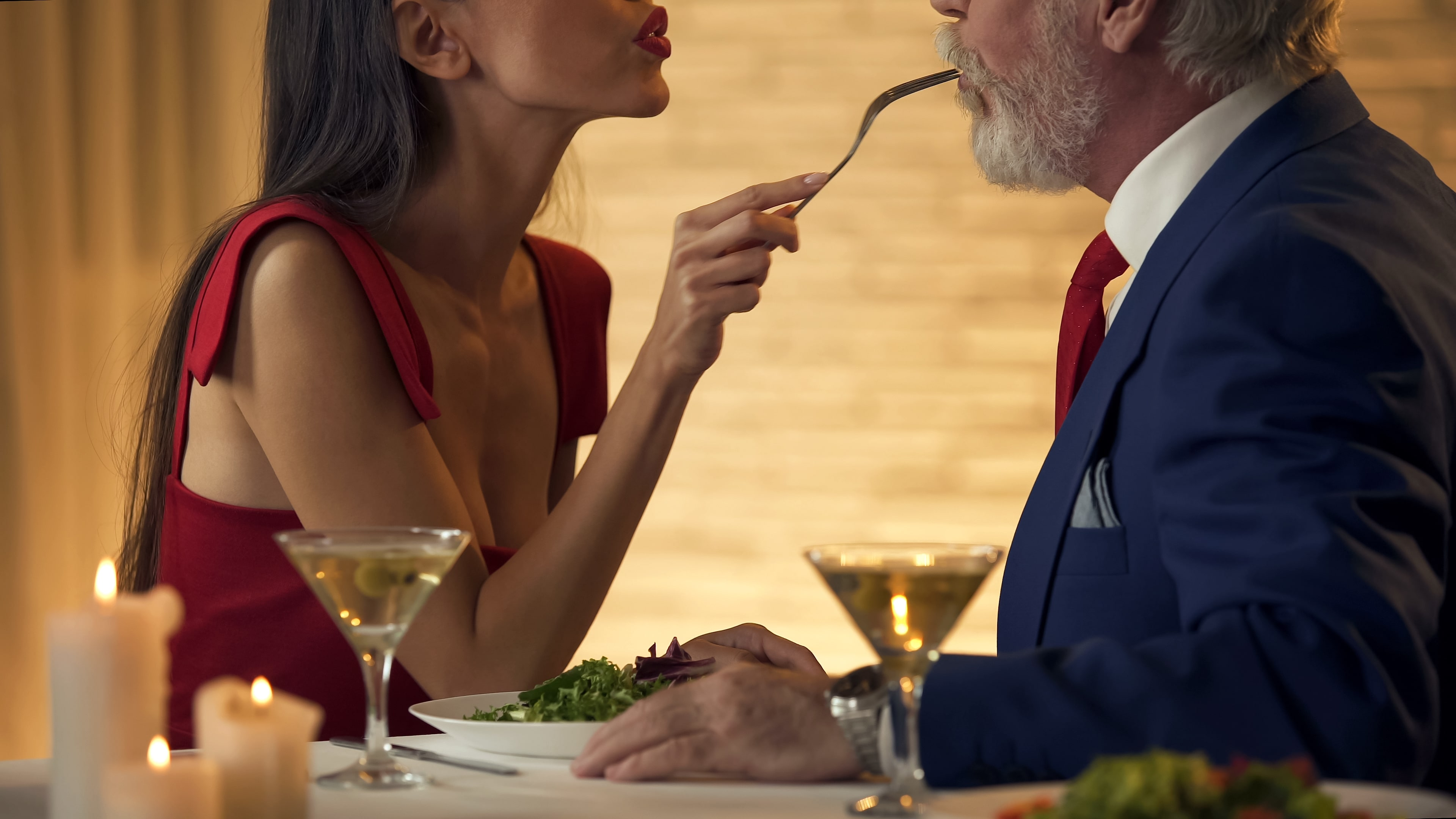 young woman feeding old man dinner
